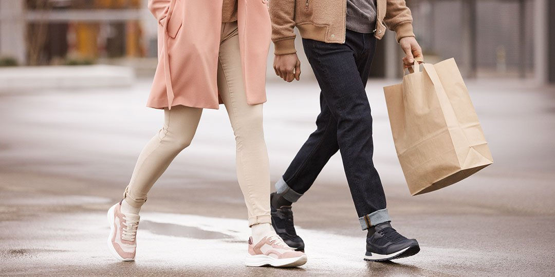 Legs and feet of a couple walking, carrying shopping bags
