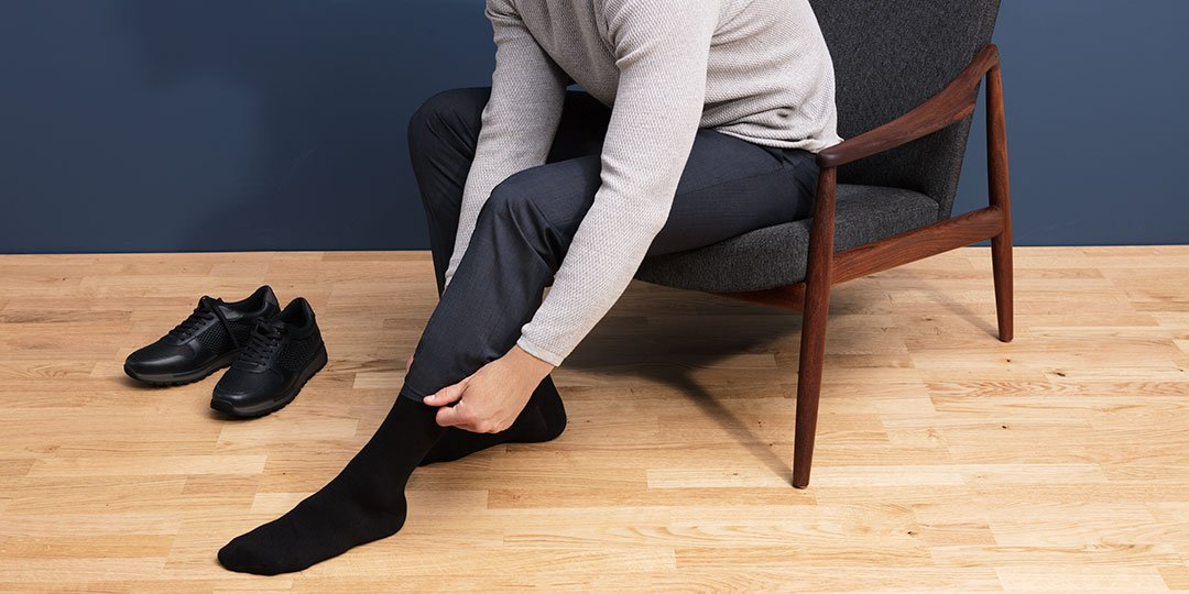 Man sitting on a low chair putting on compression socks
