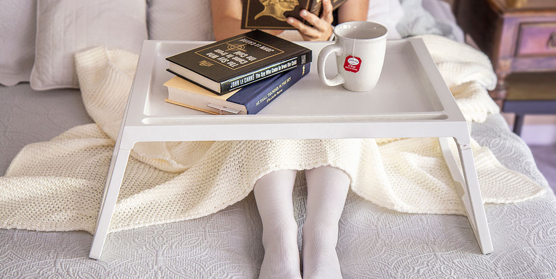 Woman with compression stockings sitting in bed, tray full of books
