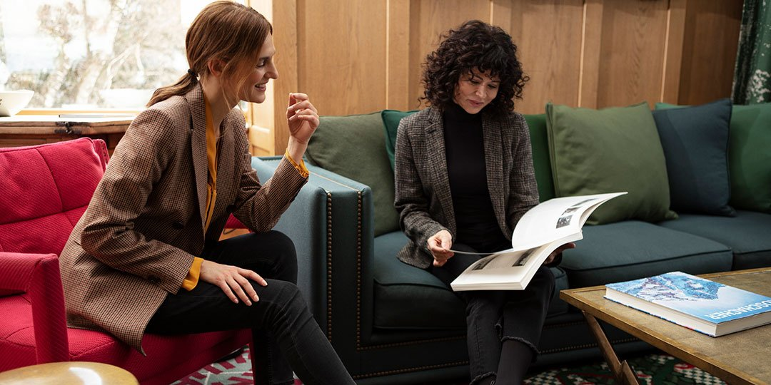 Two woman on sofas look into a book