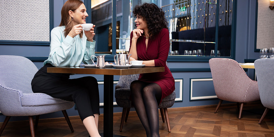Two women sitting in a cafe chatting