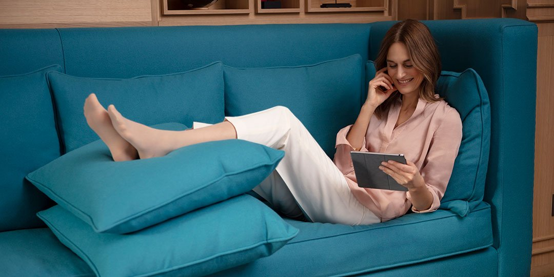 Woman sitting on turquoise sofa elevating legs