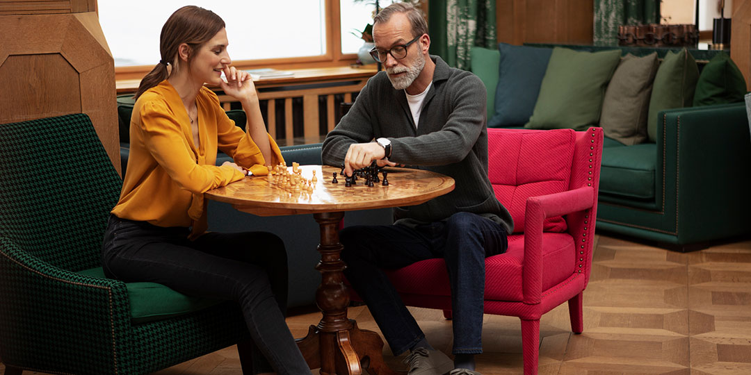Man and woman playing chess in a lobby