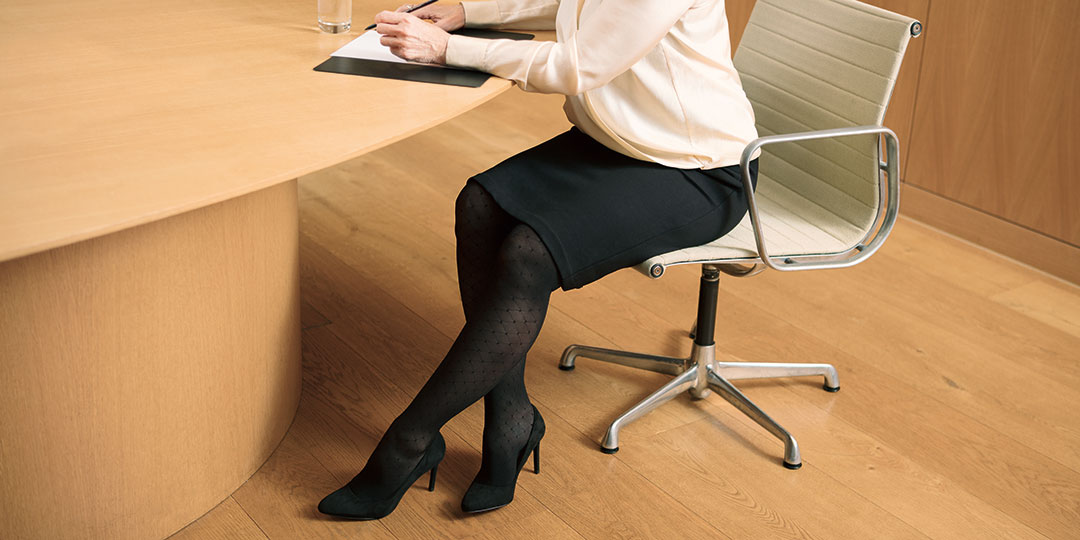 Woman in skirt sitting at a desk