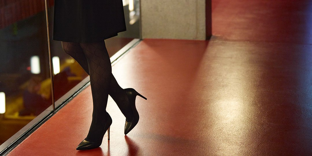 High-heeled woman in dark compression stockings on glowing floor